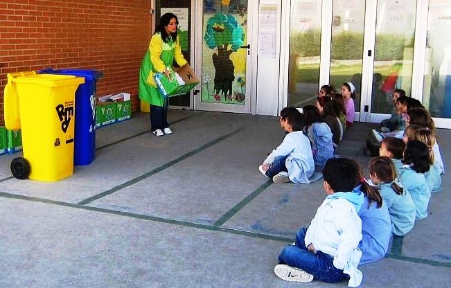 Imagen de niños y niñas aprendiendo a utilizar los contenedores y papeleras para recogida separada