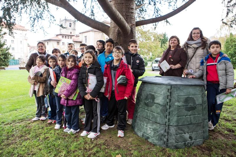 Imagen de alumnos de un centro escolar junto a una compostadora de COGERSA