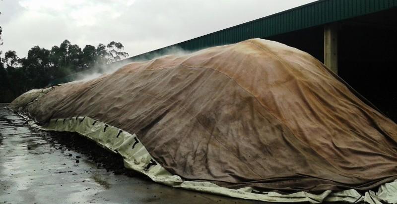 Foto del compostaje en COGERSA de una pila de lodos bajo membrana con ventilación forzada