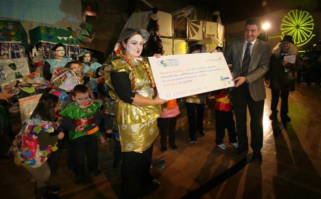 El colegio Jovellanos de Vegadeo recibe el cheque de mano del representante de Cajastur